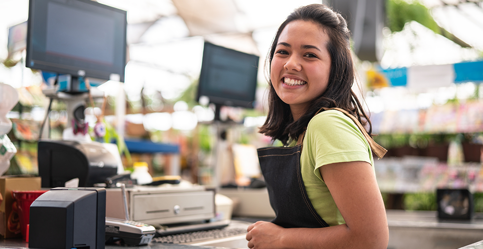 woman smiling behind cash register in a retail store